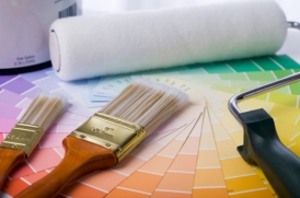 close-up image of paint brushes, roller, paint can, and paint samples